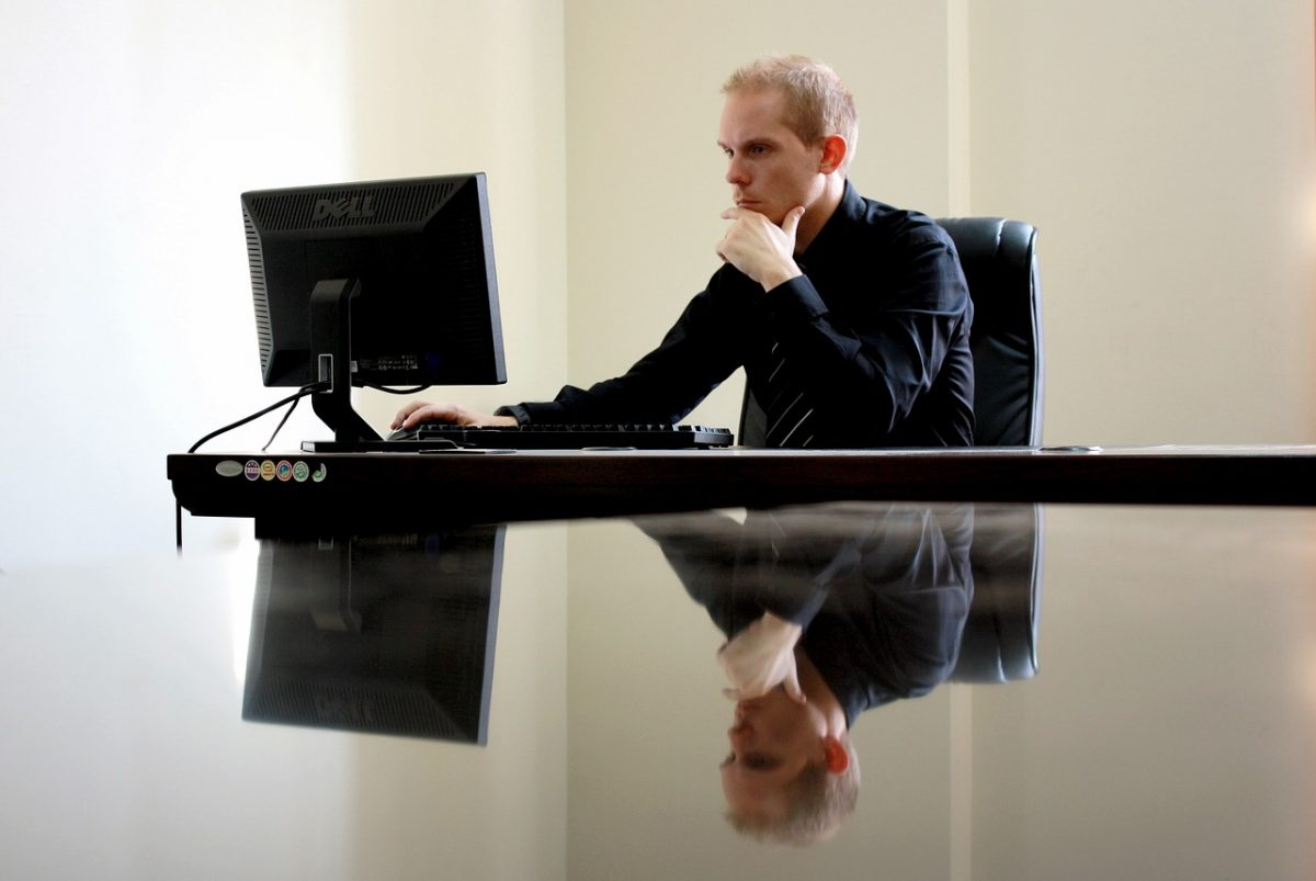 A person thinking while working on a laptop