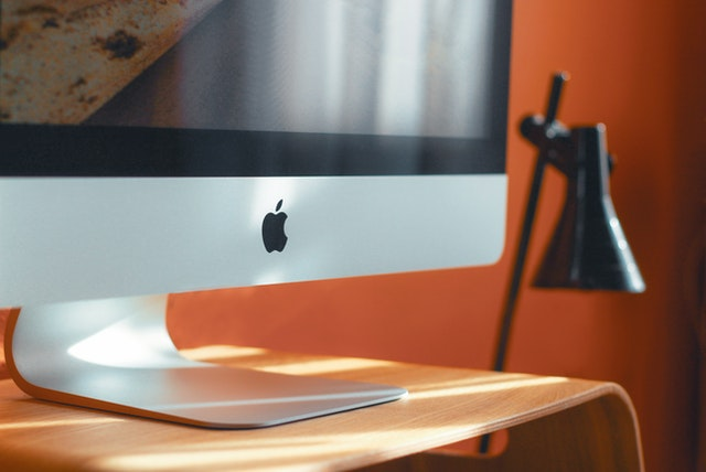 An Apple computer with a visible logo next to a lamp